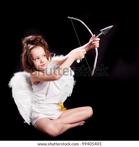 cute  six year old girl  dressed as a cupid with white wings, bow and arrow, isolated against black studio background - stock photo