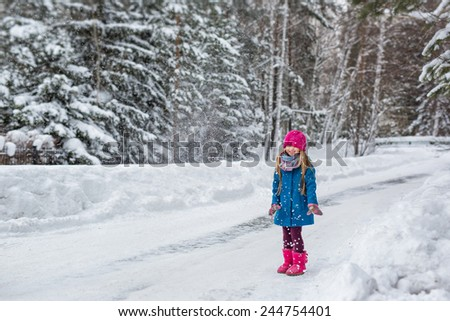 Cute six year old girl dressed in a blue coat and a pink hat and boots throws snow and laughs - stock photo