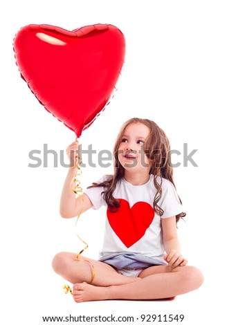 cute six year old girl wearing a T-shirt with a big red heart, isolated against white background - stock photo