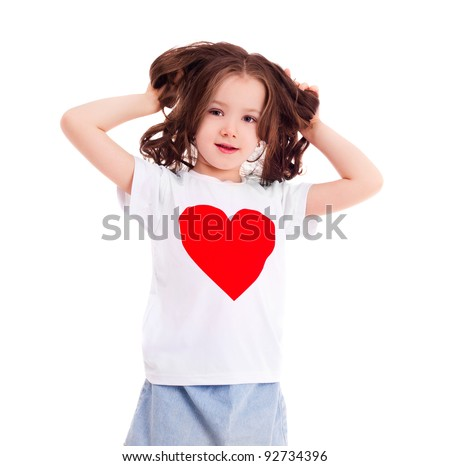 cute six year old girl wearing a T-shirt with a heart, isolated against white background - stock photo