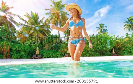 Cute slim female wearing stylish blue swimsuit comes into sea, enjoying summer vacation on Maldives island, joy and fun concept - stock photo