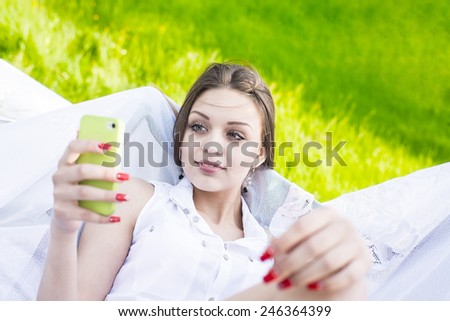 Cute slim girl looking at cell screen read book or watch video on summer fresh green grass background Portrait of Beautiful young adult caucasian woman reading a message on mobile phone  - stock photo