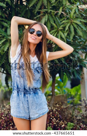 Cute slim tanned girl standing near tree. She wears white t-shirt, denim shorts and black sunglasses. She has long dark straight hair. She smiles and holds her hands on her head.  - stock photo