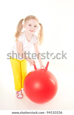 cute sly little girl doing gymnastic exercise with ball - stock photo