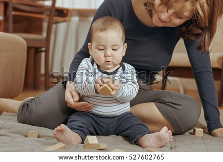 Cute small baby boy playing with educational wooden blocks in different shapes watched closely by his devoted young mother
