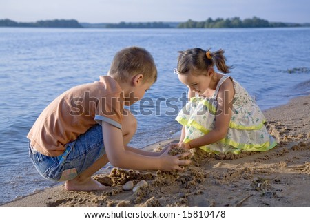 Cute small boy and girl playing in sand on seashore - stock photo
