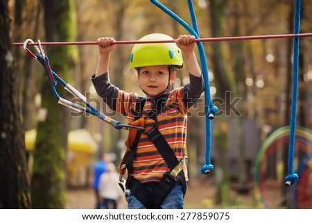Cute small boy enjoying a day in a climbing adventure activity park - stock photo