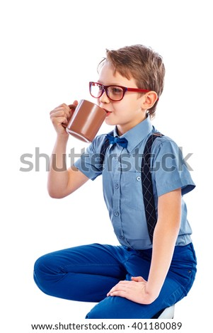 Cute small boy in glasses drinking cup of tea, coffee or juice. Looking into the distance. Isolated on a white background. - stock photo