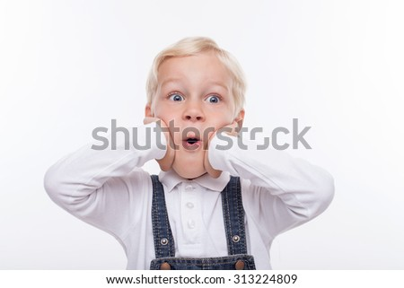 Cute small boy is looking forward with shock. He is standing and touching his face with amazement. His mouth is wide open. Isolated on background