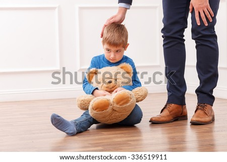 Cute small boy is sitting on flooring with sadness. His father is going to work. The man is stroking the head of child with love. The boy is embracing a teddy bear - stock photo