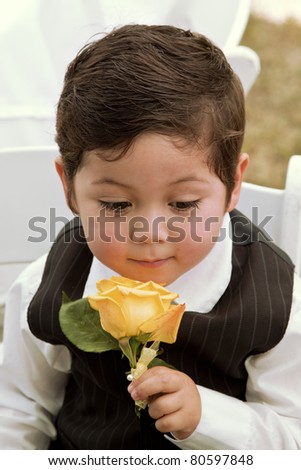 Cute small boy smelling a rose at a wedding