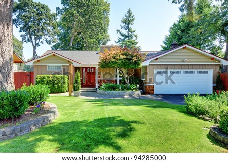 Cute small brown rambler house with red door and white garage door - stock photo