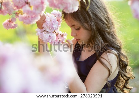 Cute small brunette girl smelling flowers standing amid pink japanese cherry blossom in broad daylight in the garden copyspace, horizontal picture - stock photo