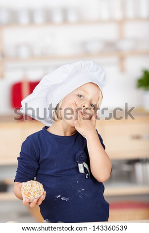 Cute small chef in an over sized chefs toque standing looking at the camera licking her fingers while cooking in the kitchen - stock photo