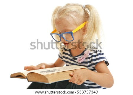 Cute small girl in glasses reading book on white background