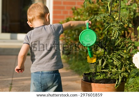 Cute Small Girl with Watering Can in Garden