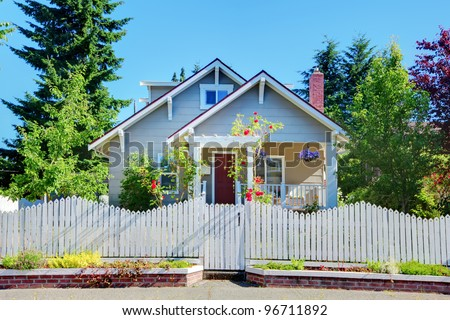 Cute small grey old craftsman style house with white fence. - stock photo