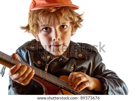 Cute small kid learning to play guitar with great concentration. White background, copy space. - stock photo