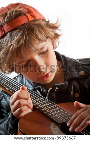Cute small kid playing guitar with great concentration and attitude. White background, copy space. - stock photo