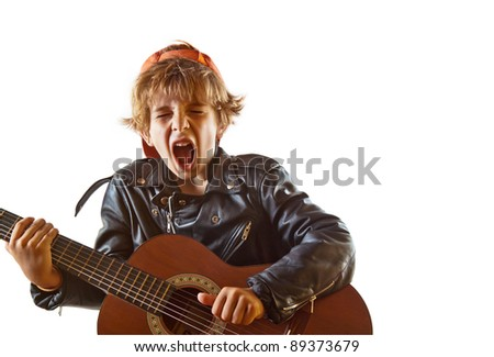 Cute small kid playing guitar with great concentration and attitude. White background, plenty of copy space.