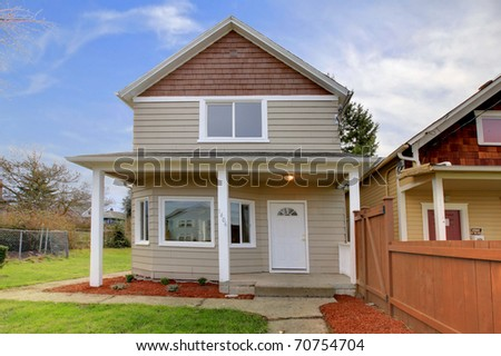 Cute small new beige house with covered front entrance - stock photo