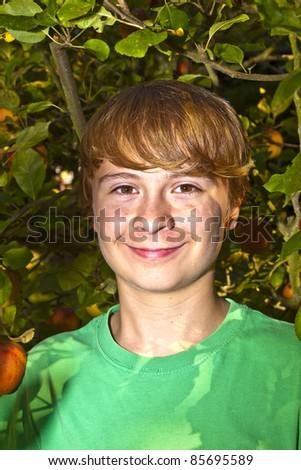 cute smart boy in the garden under the  tree - stock photo