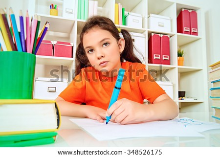 Cute smart girl sitting at the desk with school books and making her lessons. Education.