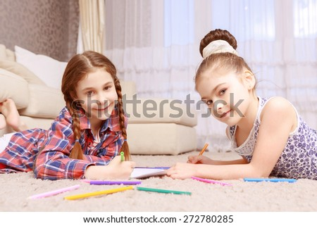 Cute smiles. Two smiling girls lying on carpet and drawing with help of colorful crayons.