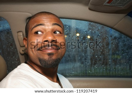 Cute smiling African American man driving car - stock photo