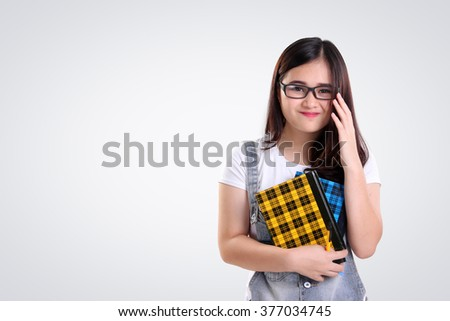 Cute smiling Asian school girl with nerd glasses holding some books, on white background for copy space - stock photo