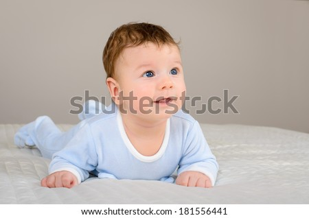 Cute smiling baby boy in bed lying on his belly and looking at the side of camera
