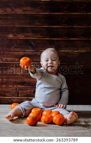 Cute smiling baby boy is offering you one fresh juicy mandarin  - stock photo