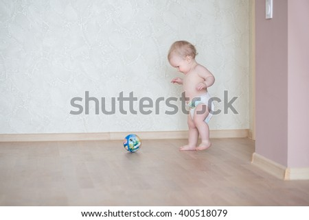 Cute smiling baby boy learning to walk and make his first steps and play with ball - stock photo