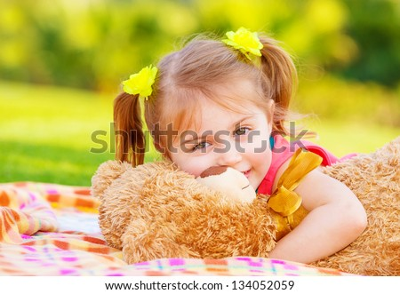 Cute smiling baby girl hugging soft bear toy, sweet kid having fun outdoors in day care, laying down on green grass in spring - stock photo