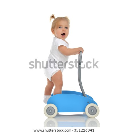 Cute smiling baby girl toddler with toy walker make first steps isolated on a white background - stock photo