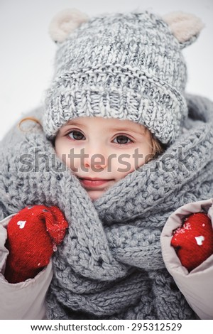 cute smiling baby girl winter close up vertical portrait in warm knitted hat and scarf and red gloves - stock photo