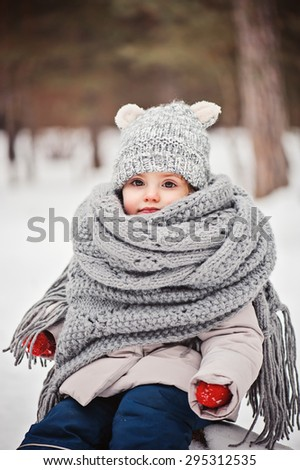 cute smiling baby girl winter vertical portrait in warm knitted hat and scarf and red gloves - stock photo
