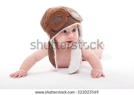 cute smiling baby in the cap of the pilot is flying on a white background. Photo with artistic blur and depth of field - stock photo
