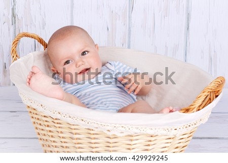 Cute smiling baby lying in wicker basket - stock photo