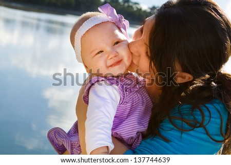 Cute smiling baby receiving a kiss from her mom by a lake - stock photo