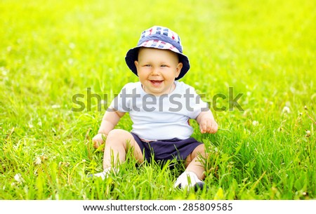 Cute smiling baby wearing a hat sitting on the grass in sunny summer day - stock photo