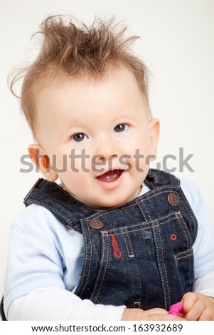 cute smiling baby with fancy haircut in studio - stock photo