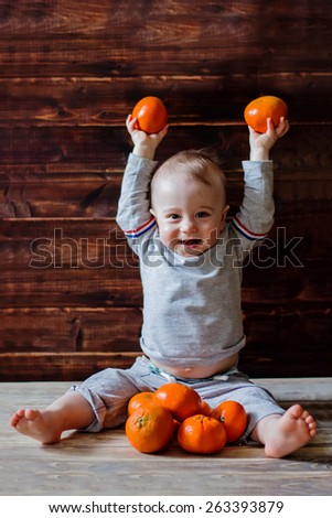 Cute smiling baby with mandarins in hands  - stock photo