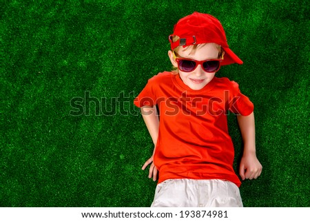 Cute smiling boy in bright summer clothes lying on a grass. Holiday. - stock photo