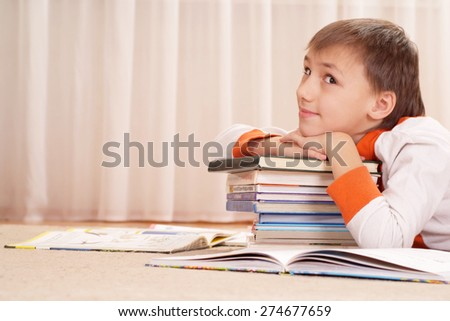 Cute smiling boy with books studying at home - stock photo