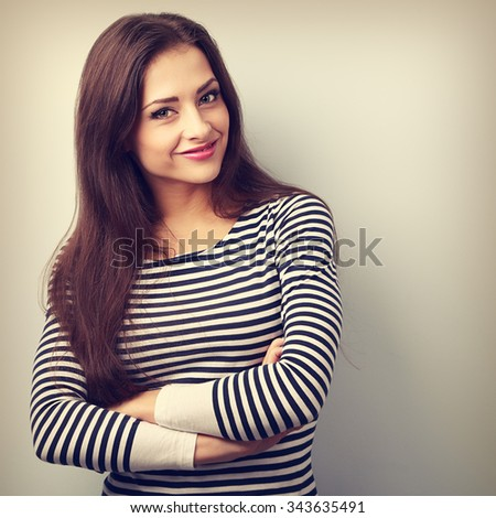 Cute smiling casual woman with folded hands looking happy on blue background with empty copy space. Vintage portrait - stock photo