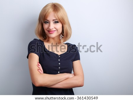 Cute smiling casual woman with folded hands looking happy on blue background with empty copy space - stock photo