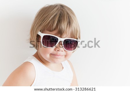 Cute smiling Caucasian little girl in shirt and sunglasses on white wall background, closeup studio portrait - stock photo