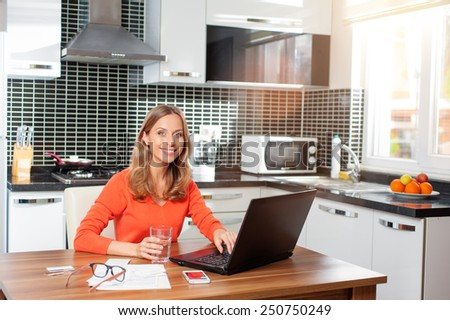 Cute smiling caucasian woman having a glass of water while using her notebook in her kitchen looking at camera. - stock photo