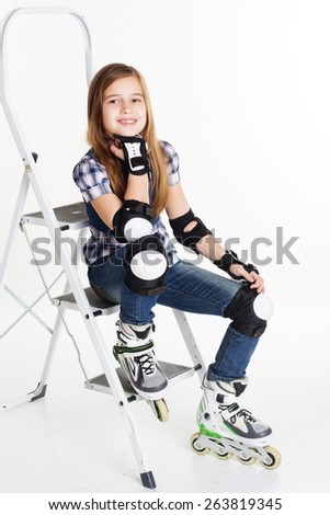 Cute smiling child girl having fun in roller skates on a white background, studio shoot - stock photo